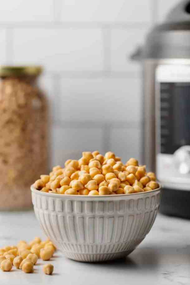 A bowl of soaked chickpeas. A jar of dried chickpeas and an Instant pot in the background