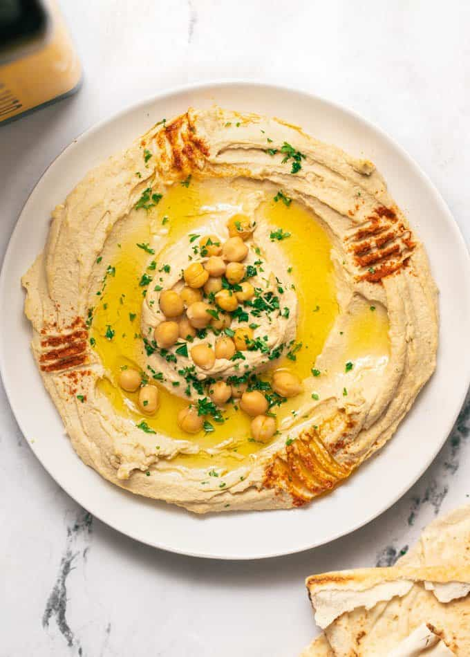 Authentic hummus swirled on a white plate topped with olive oil, chickpeas and paprika