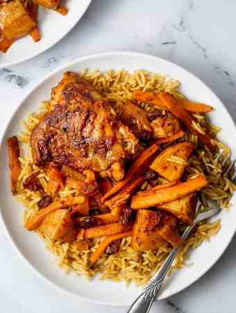 Chicken pilaf topped with potatoes, carrots, and raisin