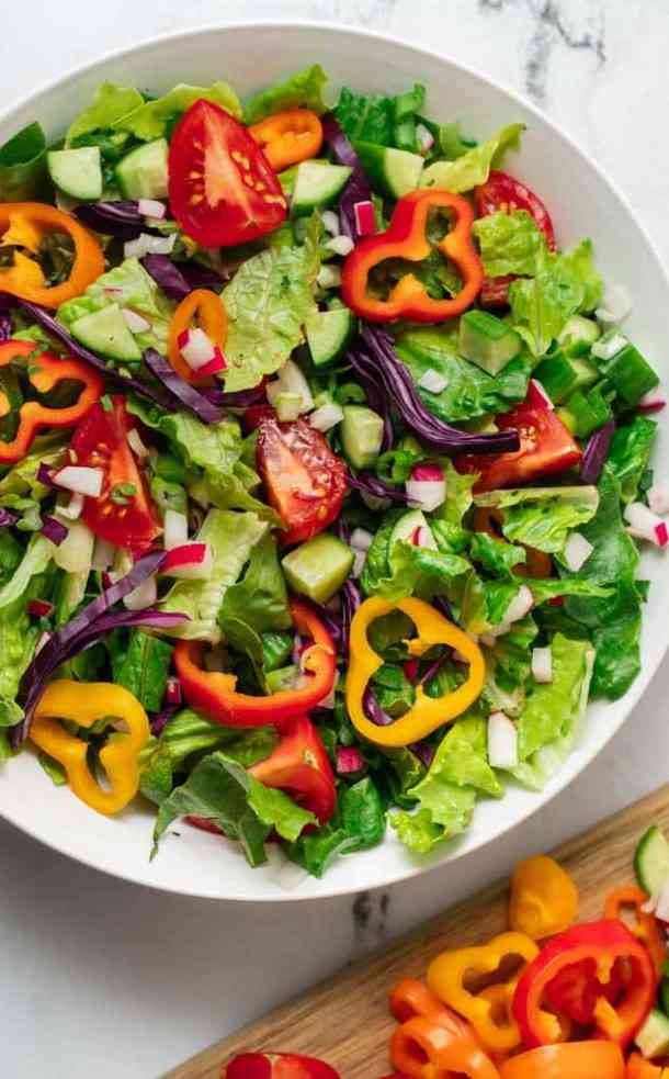 a white bowl of salad with a cutting board of cut veggies