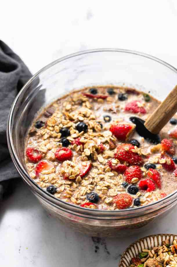 Oatmeal mixture in a glass bowl with tea towel and spatual