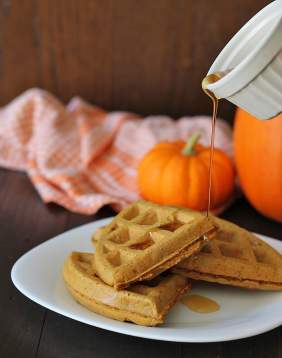 Maple syrup being poured on Vegan Gluten Free Pumpkin Spice Waffles.