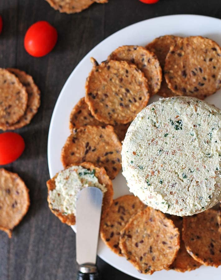 Garlic herb vegan almond cheese spread sitting on a plate with crackers.