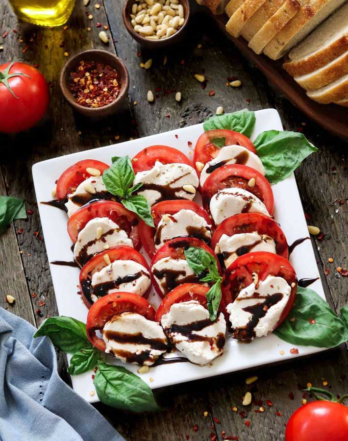 Vegan substitutes - Vegan mozzarella cheese sitting on a plate with sliced tomatoes