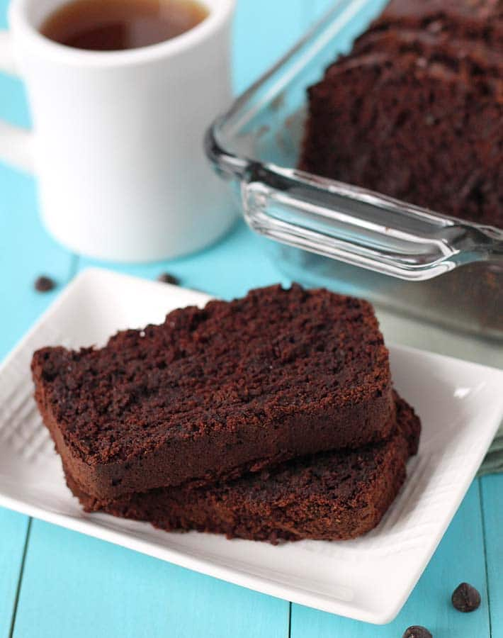 A plate of sliced Vegan Gluten Free Chocolate Zucchini Bread sitting on a plate on a blue table