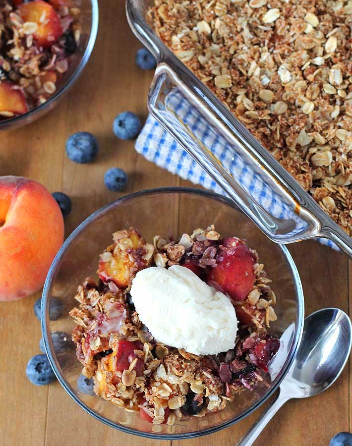 Vegan Peach Blueberry Crisp in a bowl with ice cream on top