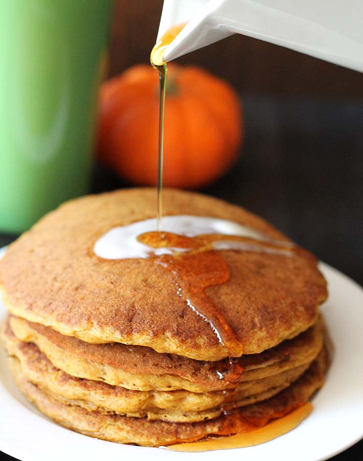 Maple syrup being poured onto a stack of vegan gluten free pumpkin pancakes