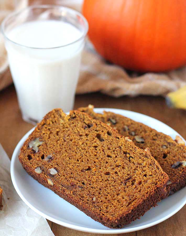 Two slices of Vegan Gluten Free Pumpkin Banana Bread on a plate with a glass of almond milk sitting behind it.