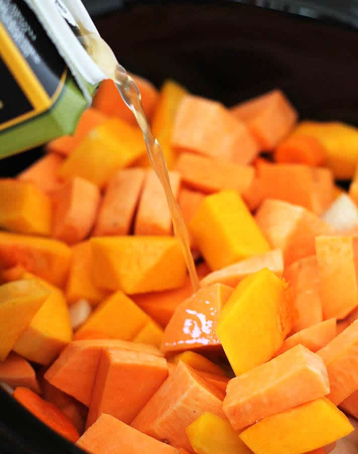 Cubes of sweet potatoes, butternut squash, carrots and onions in a slow cooker with broth being poured over top to make Butternut Squash Sweet Potato Carrot Soup.