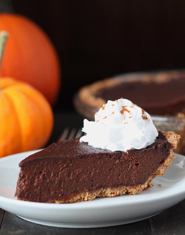 An close up shot of a slice of vegan chocolate pumpkin pie on a plate with the whole pie, minus one slice, behind to the right and fresh pumpkins behind to the left.
