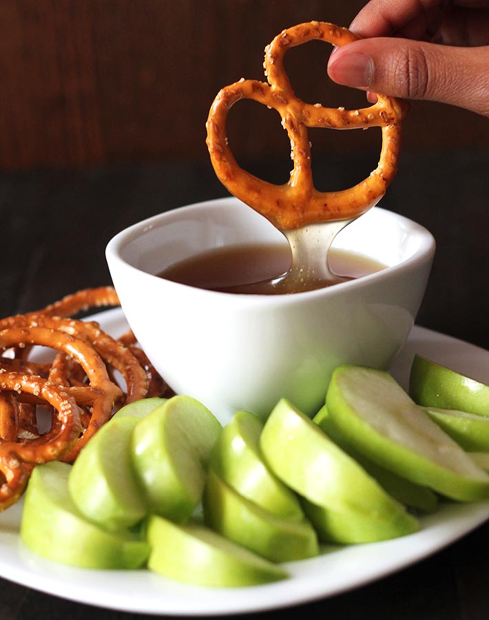 A pretzel just dipped in a bowl of vegan maple caramel sauce with sliced green apples and more pretzels sitting on a plate.