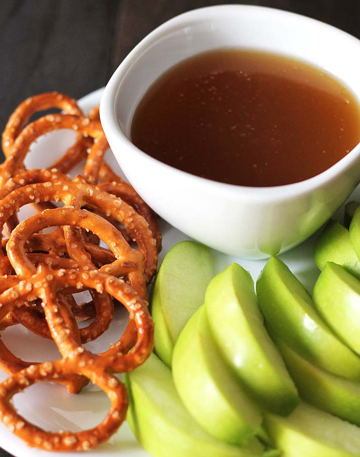 An overhead shot of a white bowl filled with dairy free maple caramel on a white plate with sliced green apples and pretzels.