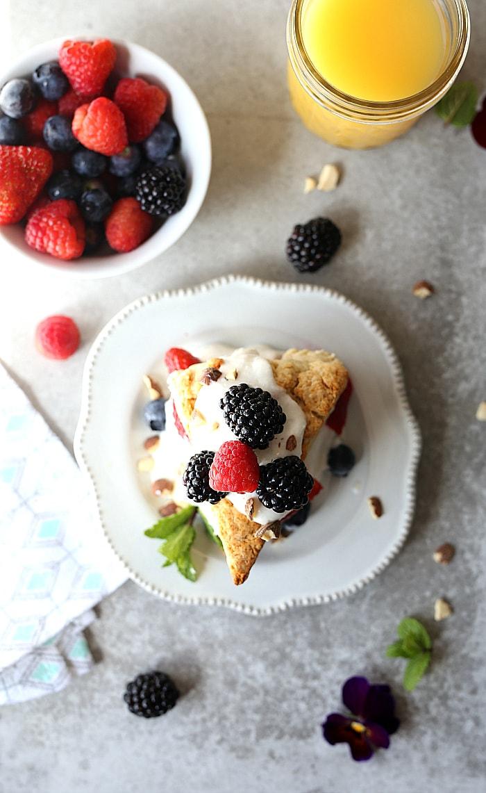 Gluten free strawberry shortcake with fresh strawberries, blueberries, blackberries and raspberries topped on a Greek yogurt honey cream filling! #strawberryshortcake #berry #recipe #glutenfree #healthy #breakfast #pastry | Delightfulmomfood.com