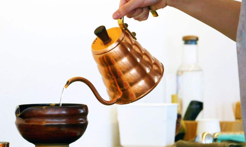 Pouring water from copper jar to a clay cup
