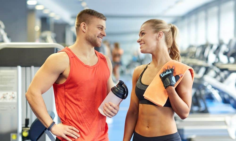 man holding reusable bottle water while talking with woman
