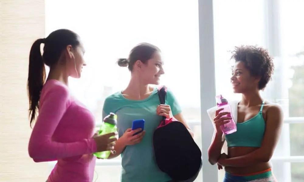 women talking in the gym holding bottle water