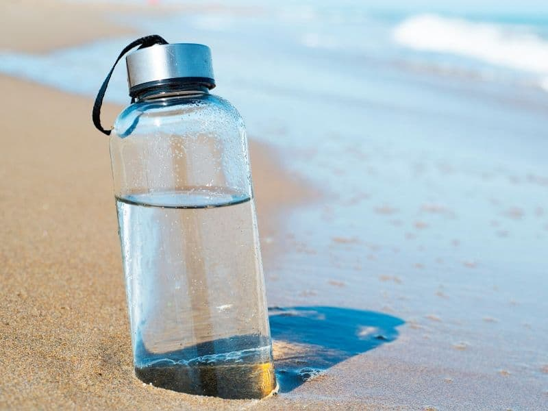 a glass reusable water bottle on the beach
