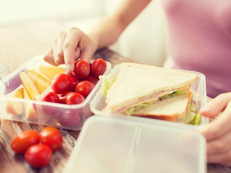 plastic food containers filled with sandwich, tomato and fries