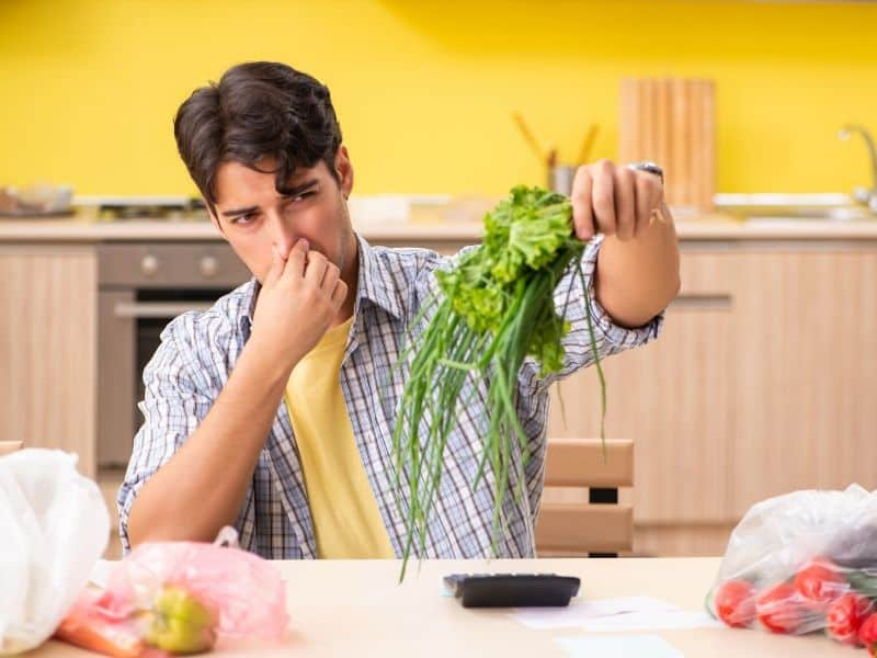a man smelling spoiled vegetables