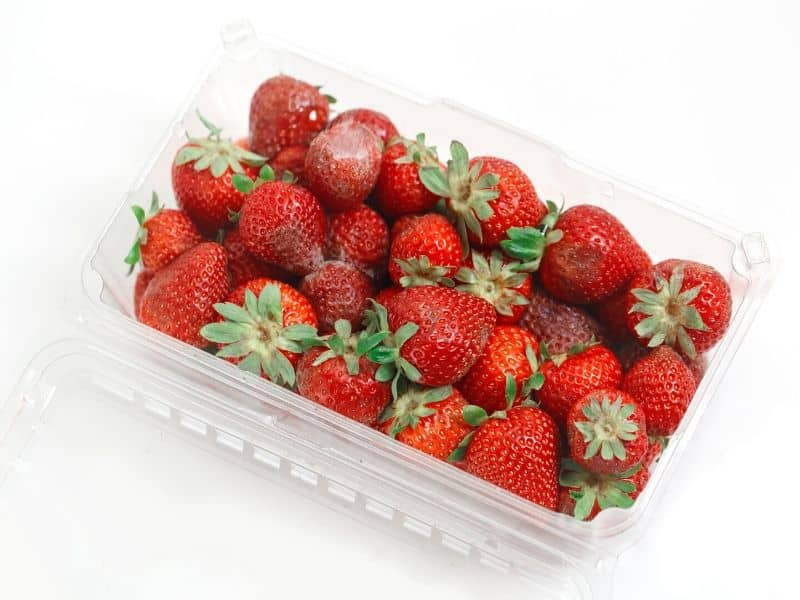 spoiled strawberry in the plastic container
