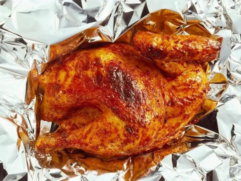 Half a grilled chicken on aluminium foil