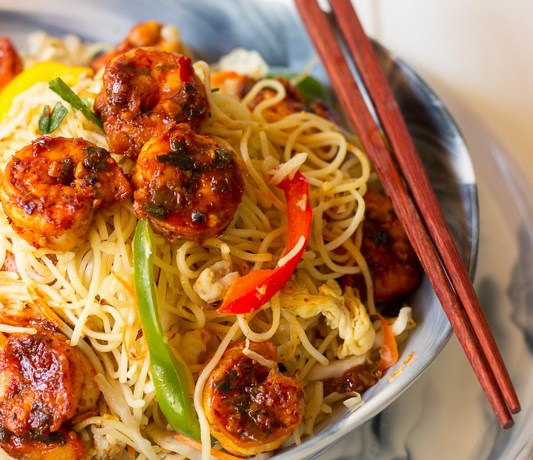 Close up of Hakka noodles wok tossed with vegetables, sauces and chilli garlic prawns in a bowl