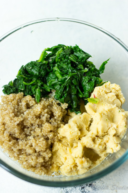 In a bowl mix spinach, chickpeas paste and cooked quinoa for making quinoa patties.