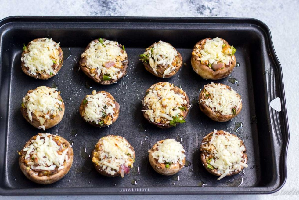 Party appetiser Cheese stuffed mushrooms lined in a baking tin ready to go into oven to get baked