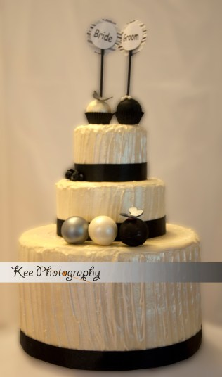 white-chocolate-wedding-cake-with-cake-pop-topper-black-silver-detail