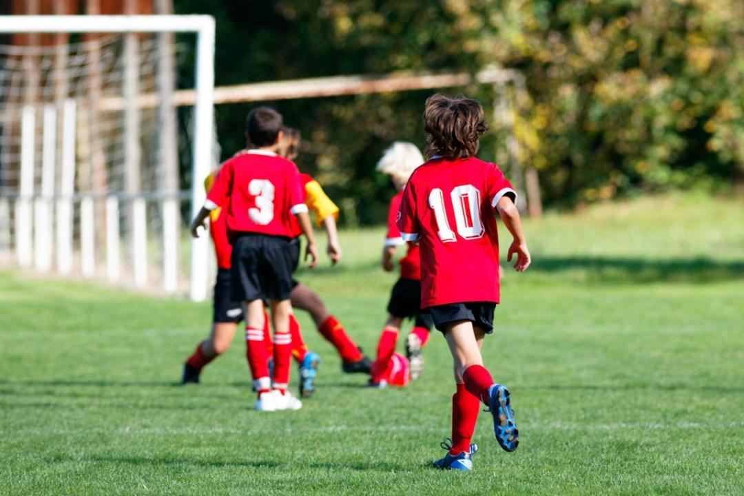 niños juegan al futbol con equipacion deportiva personalizada por delmapunto
