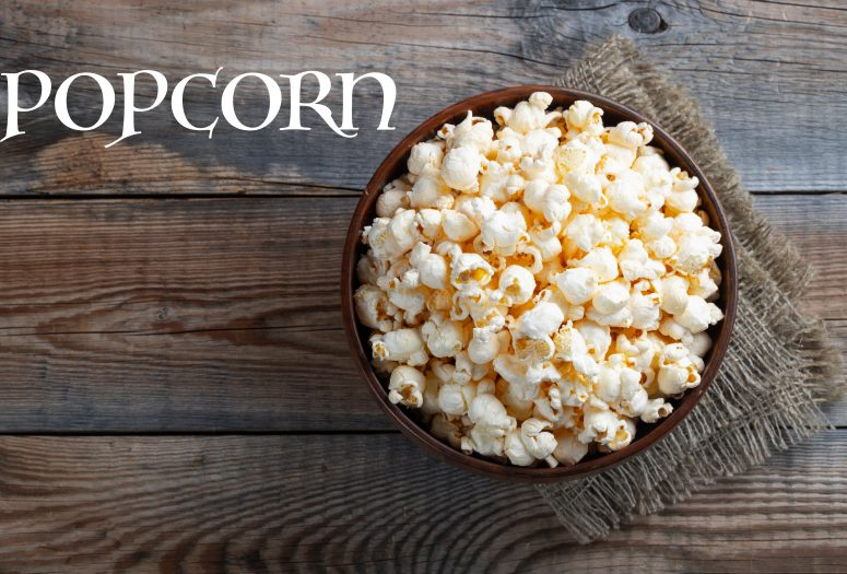A wooden bowl of salted popcorn at the old wooden table. Top view with copy space. Flat lay. Dark background.