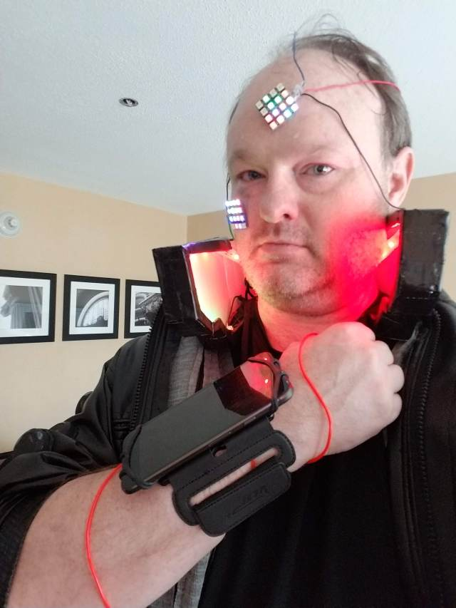 Wrist mounted smartphone, light up collar, LEDs glued to my face, and el wire on my arm. Not pictured is the bluetooth keyboard on my other wrist.