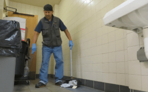 TAKING OUT THE TRASH: Julian Avila sweeps up trash in a campus restroom. PHOTO BY KRISTEN RIEDEL