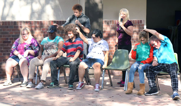 Students follow hypnotists command throughout show to raise hands and pet the person next to them.