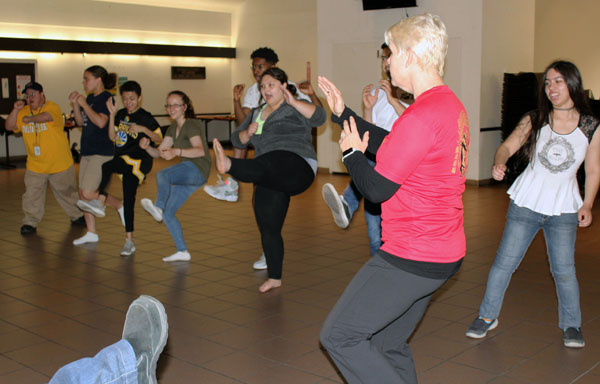 After going over key weak spots in most people, Byrd leads the group of enthusiastic students in learning how to properly front kick and back kick with both legs.