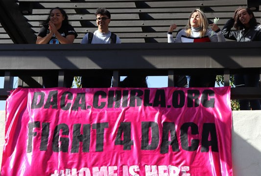 I Am/Yo Soy club President Erika Reyes, third from left, speaks during a banner drop event on the forum walkway on Oct. 9. Below, a crowd gathers to watch the banner drop. Photo by Jeff Leiva.
