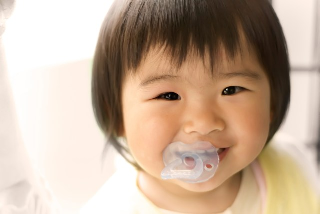 Asian toddler with pacifier in mouth