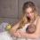 Smiling mother breastfeeding her baby in bed