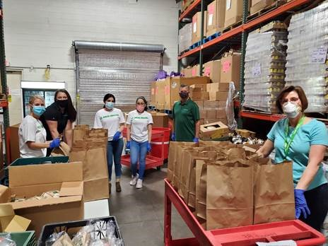 group shot of Delta Dental of Arizona employees volunteering with Desert Mission Food Bank to help others while socially distanced