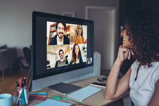 woman at computer smiles back at remote employees over video conference