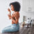 young woman sitting on kitchen counter eating a cup of probiotic rich yogurt
