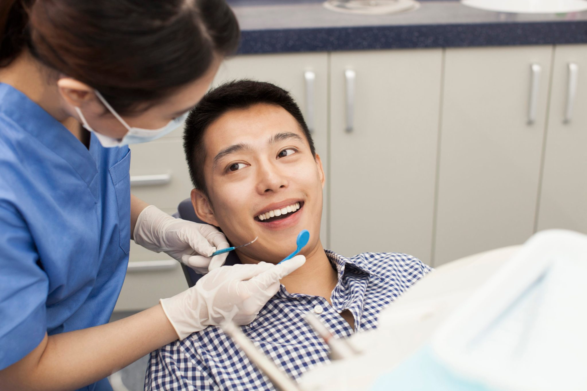 young man sitting in dentist chair during dental appointment