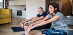 couple stretching and exercising on the floor for good health and to live longer