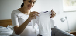 woman late in pregnancy holds up baby onesie
