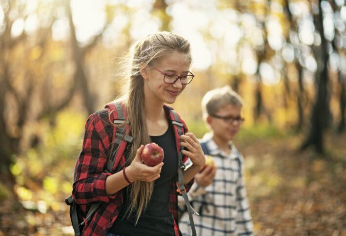 siblings hiking in the woods and eating fall food favorites like freshly picked apples
