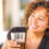 woman smiling and drinking a glass of dark soda