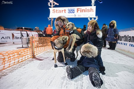 At the finish line: K300 champion Pete Kaiser and his lead dogs are greeted by his wife Bethany and son Ari at the chute after a long, hard race. photo by Greg Lincoln