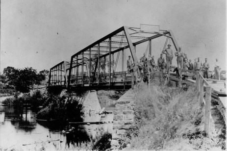 Pictured is the crew that re-planked the wood floor 1898. Included in the photo is Highway Commissioner Charles Knapp in the center of the men wearing a hat. Budd Wilson stands to the far right of the group. The photo is believed to be taken from the south bank looking north toward Delta Mills.