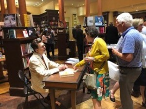 Photo from the book launch of Death of a Butterfly: Mental Health Court Diaries from September 11, 2019 at Ben McNally Books. Richard D. Schneider sits at a table, speaking with a customer.