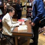 Photo from the book launch of Death of a Butterfly: Mental Health Court Diaries from Septepber 11, 2019 at Ben McNally Books. Richard D. Schneider sits at a table, signing copies of his book for a customer.
